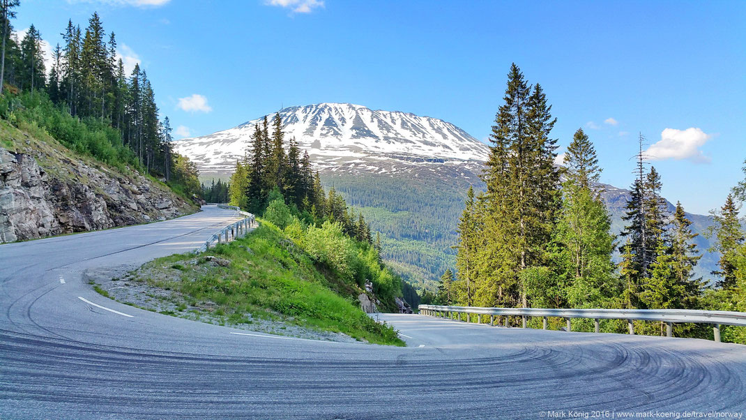Photo showing snow-capped peak of Gaustatoppen mountain with blue sky; a narrow hairpin curve in the front of the picture