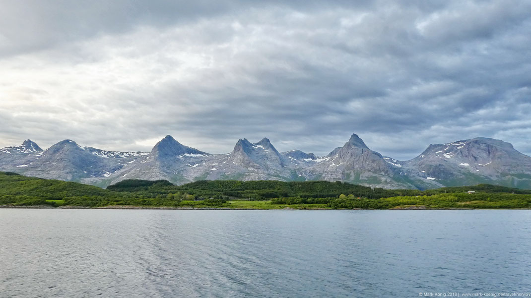 Photo of mountain peak chain Seven Sisters from the sea with nature green coastline in front and clouded sky in the background.