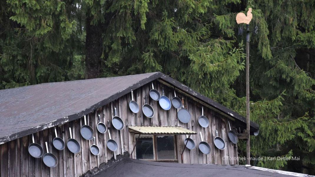 Ein Bild mit vielen Pfannen an einem Nebengebäude und ein Goldener Hahn an einer Stange