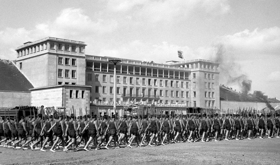 Stadion vor Einweihung mit Eingangsgebäude und Sportlern im Verband vorbei laufend