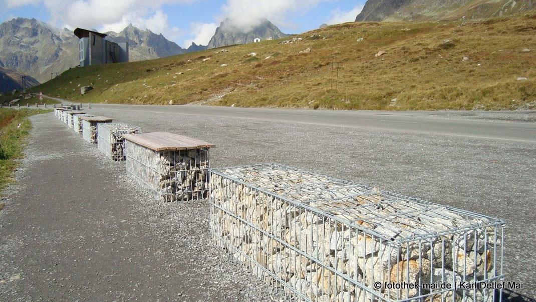 In den Alpen Österreichs entdeckt: Steine in Drahtkörben als Absperrung an der Straße, die teils als Sitzbank nutzbar sind.