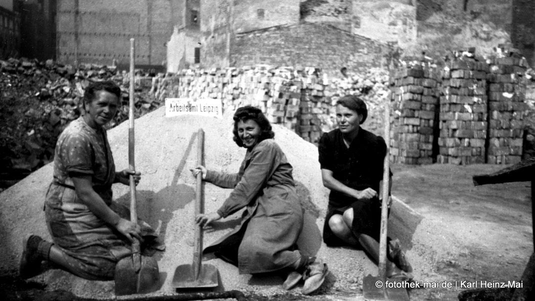 Drei Trümmerfrauen mit Schaufeln posieren dem Fotografen zwischen Trümmerschutt, Ziegelstapeln und Sandhaufen