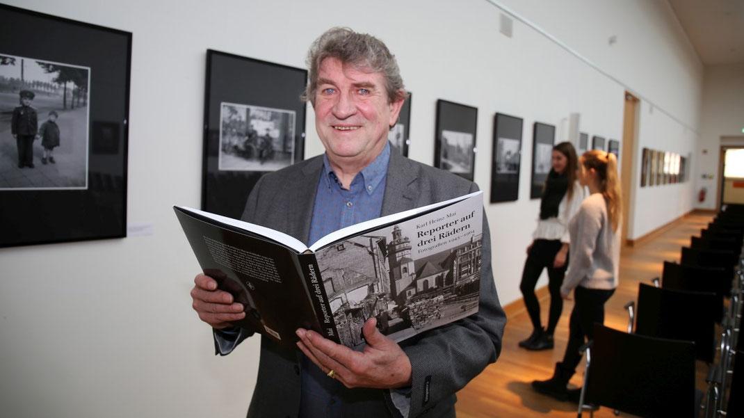 Oberlichtsaal, Portrait Karl Detlef Mai mit Bildband in der Hand - gerahmte Bilder an der Wand
