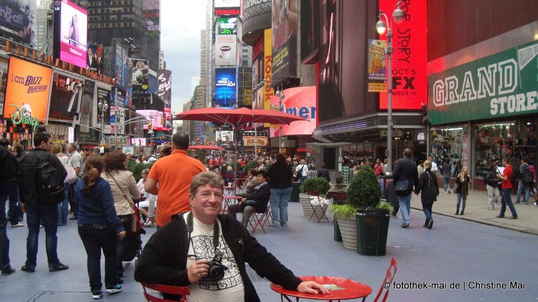 Fotograf Mai sitzt in Fußgängerbereich des Broadways in New York auf Bistrostuhl an rotem Tisch