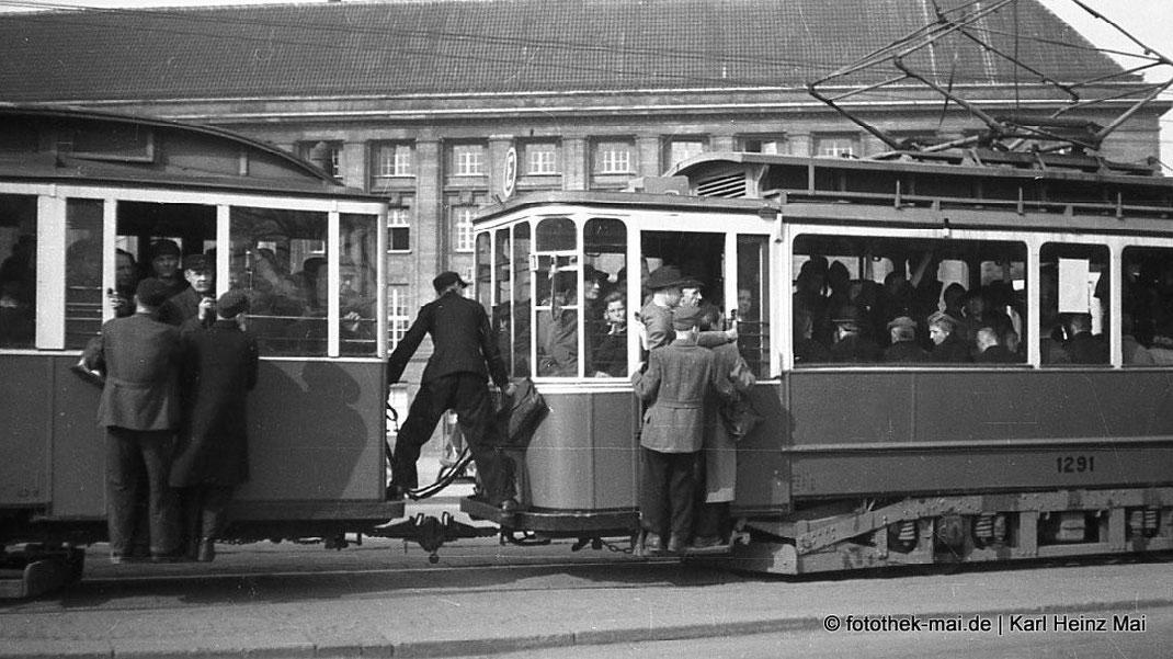 Leute fahren auf Trittbrettern mit Straßenbahn vor dem Leipziger Hauptbahnhof