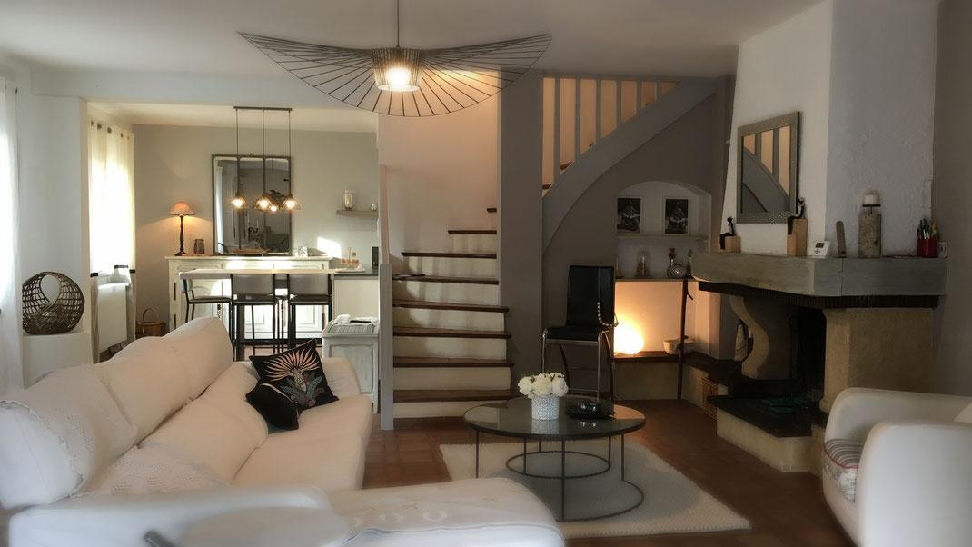 Ambiance douce et sereine pour ce grand séjour blanc et beige avec cheminée ouverte sur une cuisine contemporaine et conviviale. Suspension Vertigo.