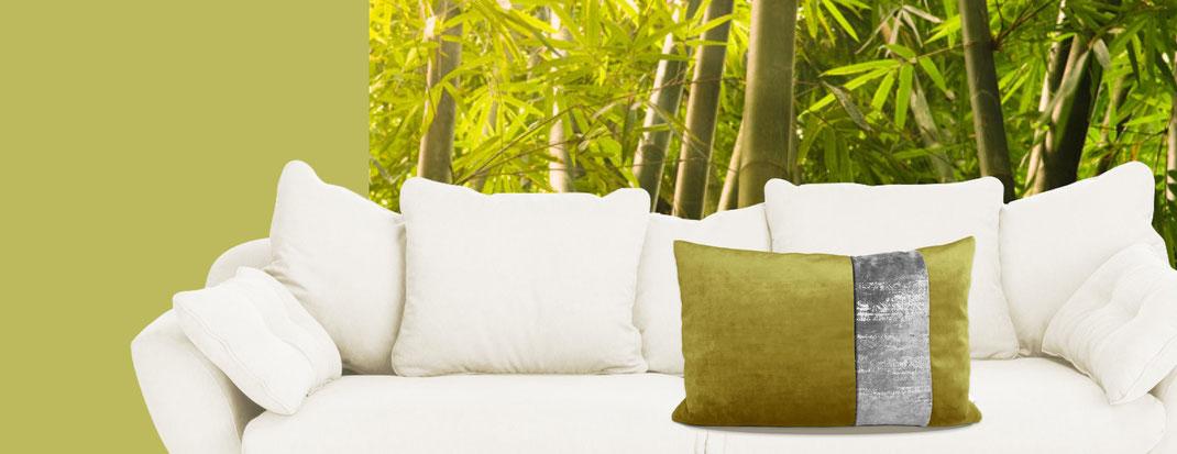grün-silbernes Natura-Kissen von Nähhörnchen auf weißer Couch vor Bambus-Fototapete