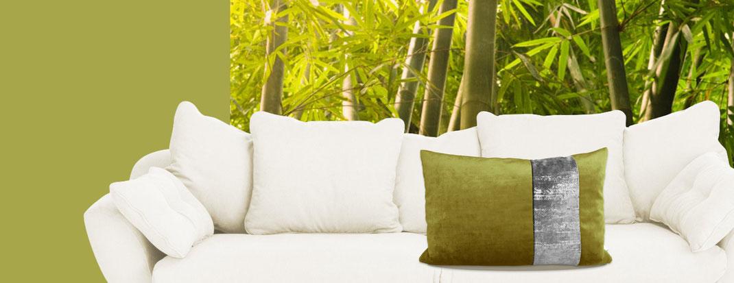 grün-silbernes Kissen auf weißer Couch vor Bambus-Fototapete