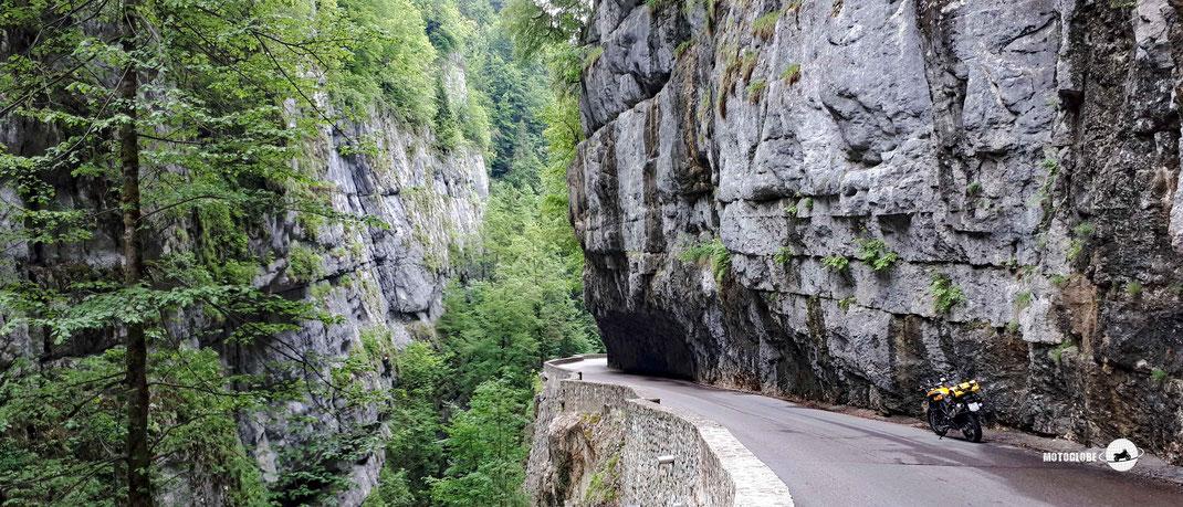 Felswand, Schmale Bergstrasse, kleine Mauer, tiefe Schlucht, gelbes Motorrad, blauer Himmel