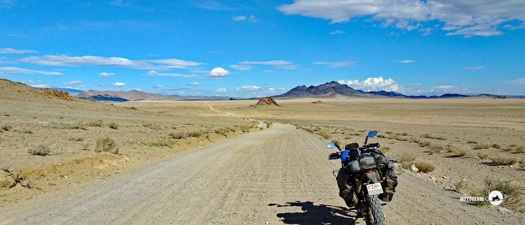 Teerstrasse, Harley Davidson Motorrad, grüne Steppen, Berge im Hintergrund, blauer Himmel
