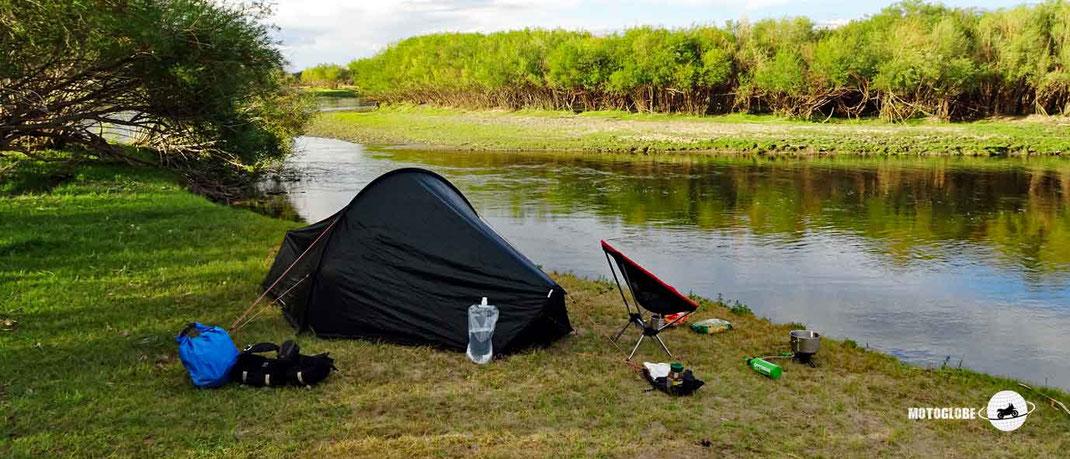 Grünes Zelt, grüne Wiese, Fluss, Bäume und Wäld, Camping Stühl, Kocher, Wasserflasche und Schutzbeutel