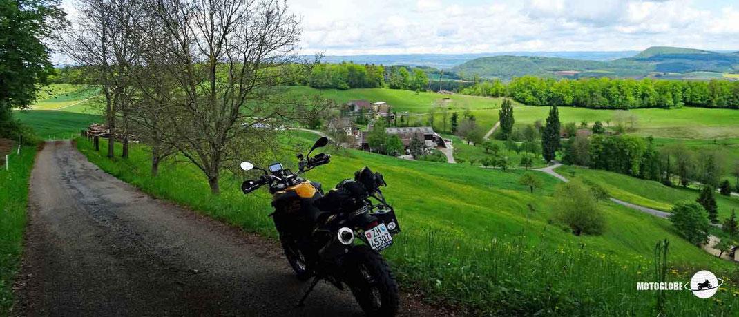 Kleine Teerstrasse, grüne Wiesen, Bäume, Bauernhaus, Grüne bewaldete Hügel, blauer Himmel mit weissen Wolken, Motorradlenker