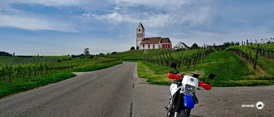 Motorradtour Schaffhausen, blau-weisses Motorrad Suzuki DRZ 400, Teerstrasse, grüne Reben, Kirche weiss mit Turm, Wiesen, blauer Himmel