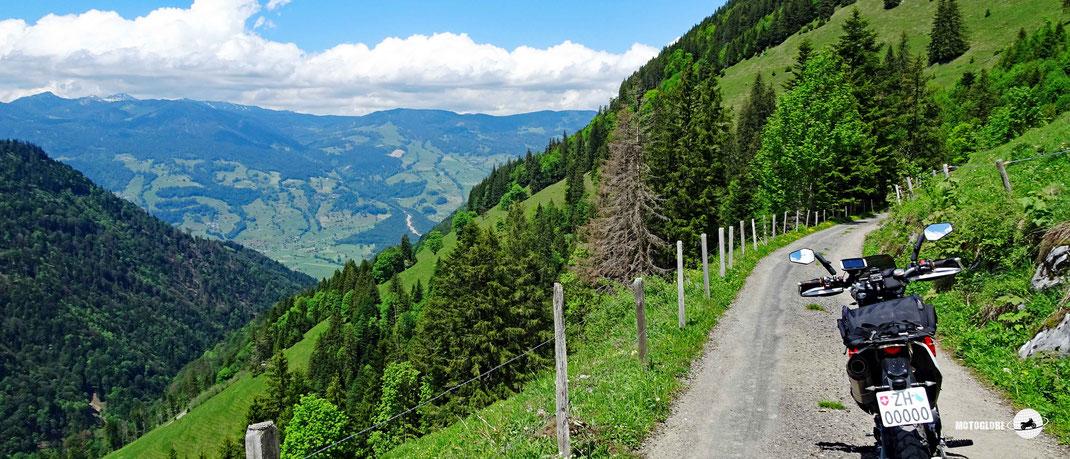 Schmales Strässchen, Motorrad, Zaun, grüne Wiesen, grüner Wälder, Hügel, Berge, Weitblick, blauer Himmel, weisse Wolken