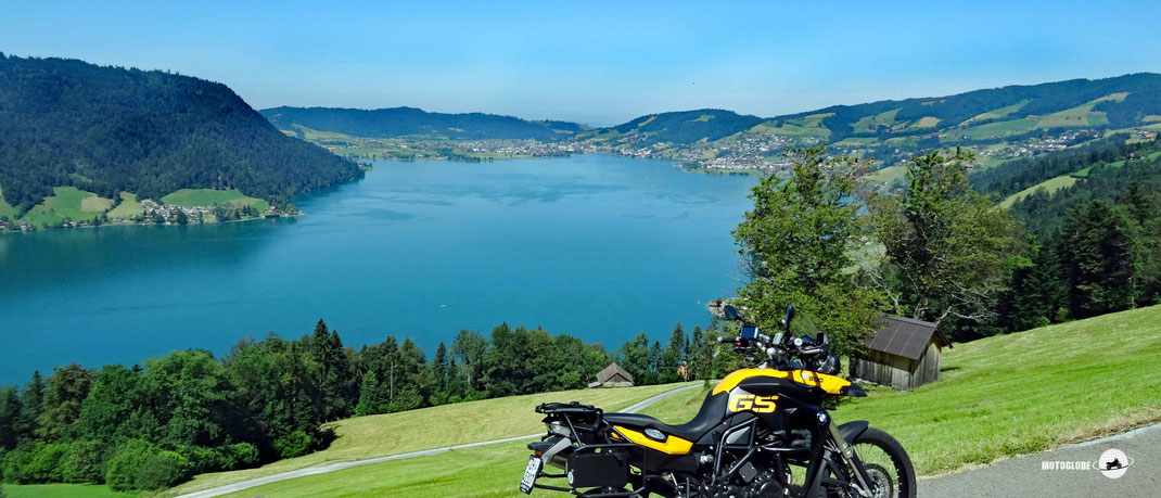 Gelbes BMW Motorrad. See. Wälder, grüne Wiesen, Häuser, blauer Himmel.