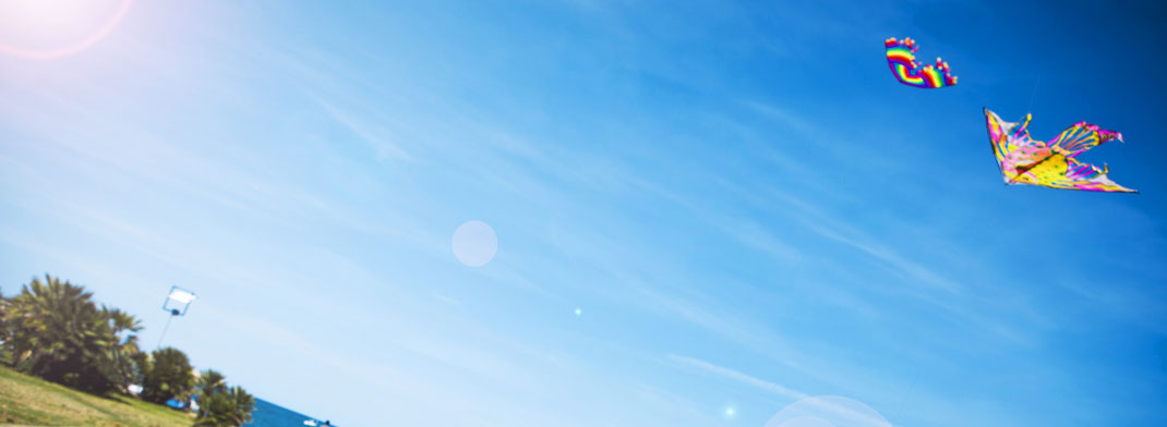 Blauer Himmel mit fliegendem Drachen, Sonnenschein und Meer