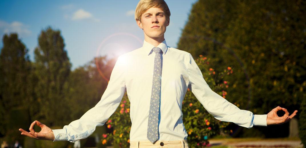 Mann in Meditationspose, in Hemd, Kravatte, blauer Himmel
