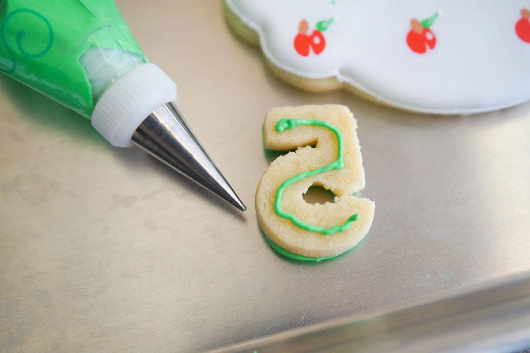 Piping Sugar onto decorated sugar cookies