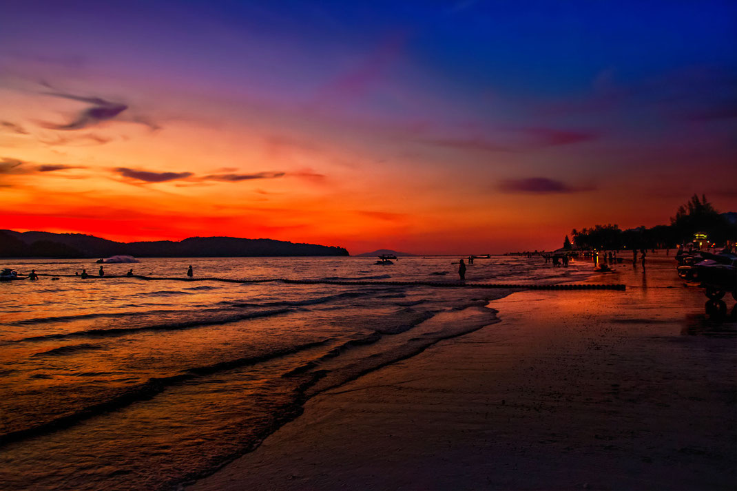 Sonnenuntergang mit orange rotem Himmel am Cenag Beach auf Langkawi-Malaysia. Einige Leute stehen im Wasser oder schwimmen. Fotos aus Malaysia kostenlos downloaden bei www.mjpics.de