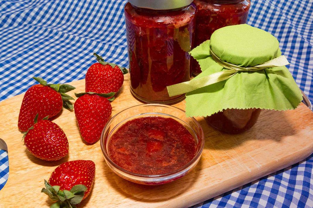 Klassische selbstgemachte Erdbeermarmelade in Gläsern, dekoriert mit frischen Erdbeeren