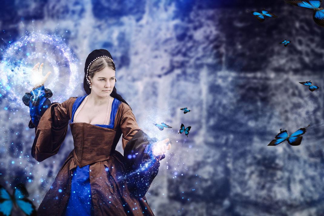 Tudor Zauberin auf Burg Hellenstein, Heidenheim. Magisches Fantasy Fotografie Shooting aus Ravensburg. Fantasievolle Bearbeitung und Retusche mit Zaubern und Schmetterlingen
