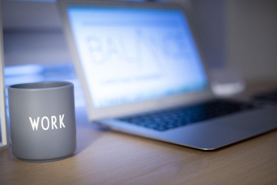 Stillleben auf dem Schreibtisch mit Laptop mit dem Balance Logo von Christiane Rademann und Tasse mit Schriftzug Work