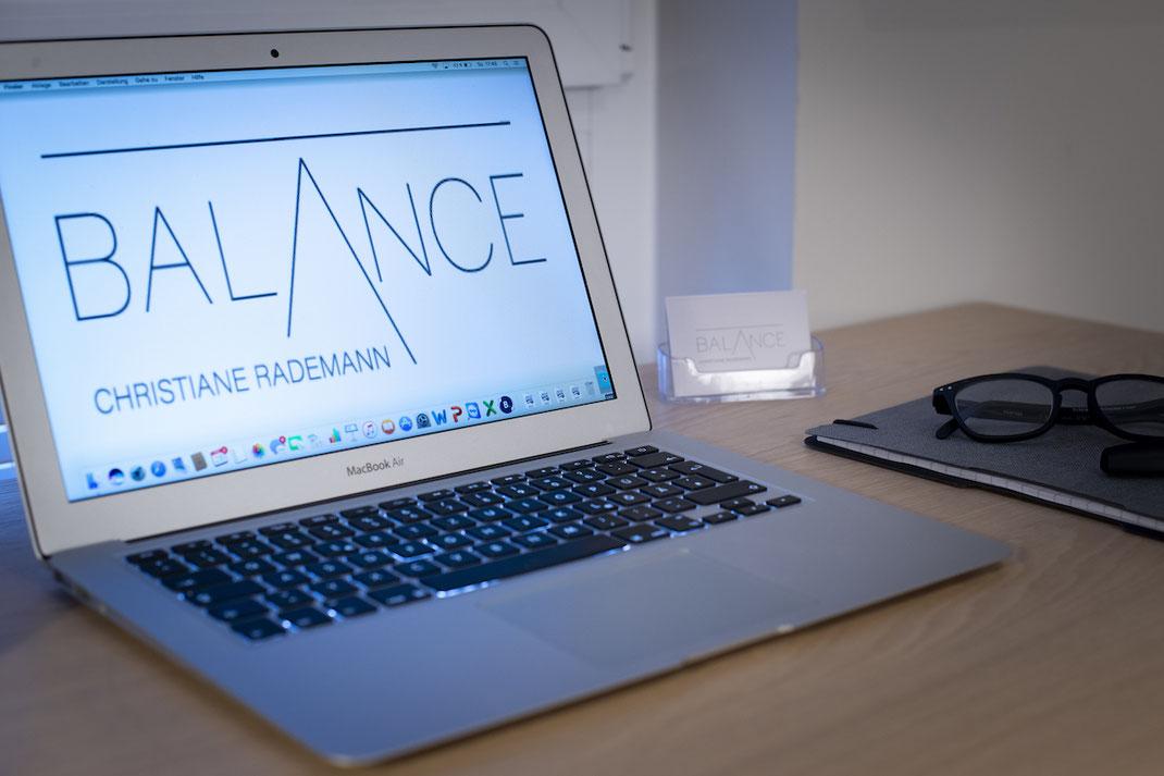 Schreibtisch-Stillleben mit Laptop, welches das Balance Christiane Rademann Logo zeigt.