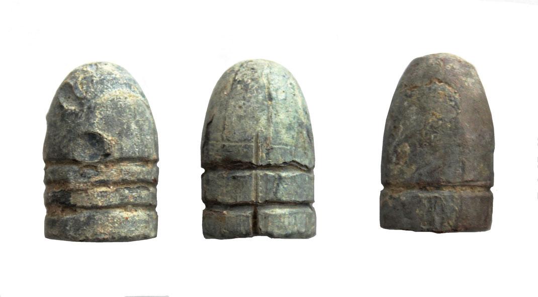 3 deutsche Bleigeschosse. Das rechte Bleigeschoss könnte ein zylindroogivales Spitzgeschoss mit schwacher Reifelung und abgeplatteter Spitze (Bayer. Infanteriegewehr, Muster 1858) sein.
