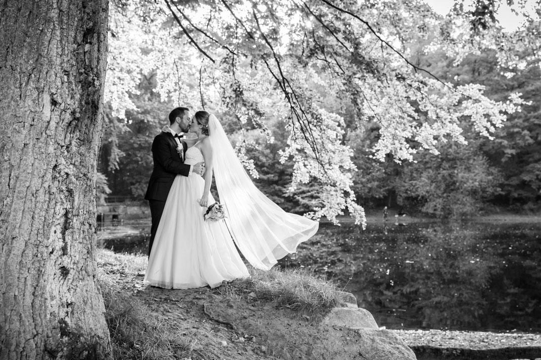 Hochzeitsbild von sensationellem Brautkleid mit Brautstrauß und Bräutigam