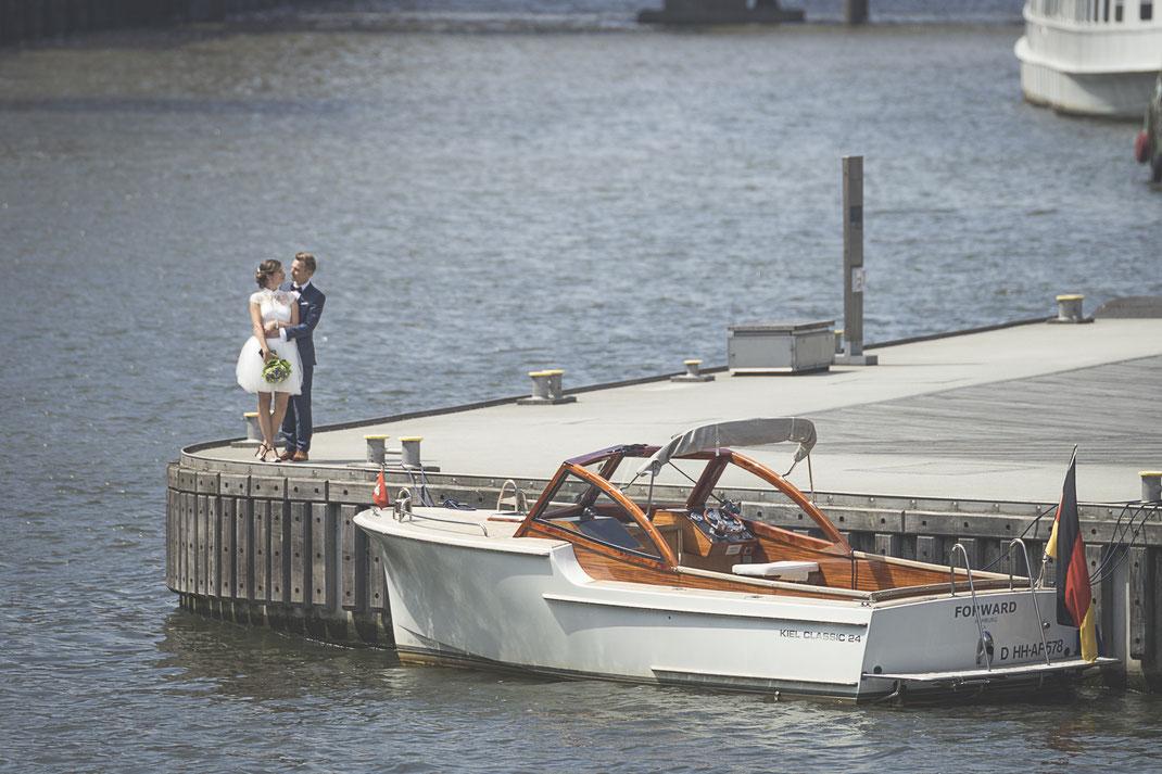 Hochzeitsfotograf Hamburg - frischgebackene Eheleute vor Mototboot in der Hafencity