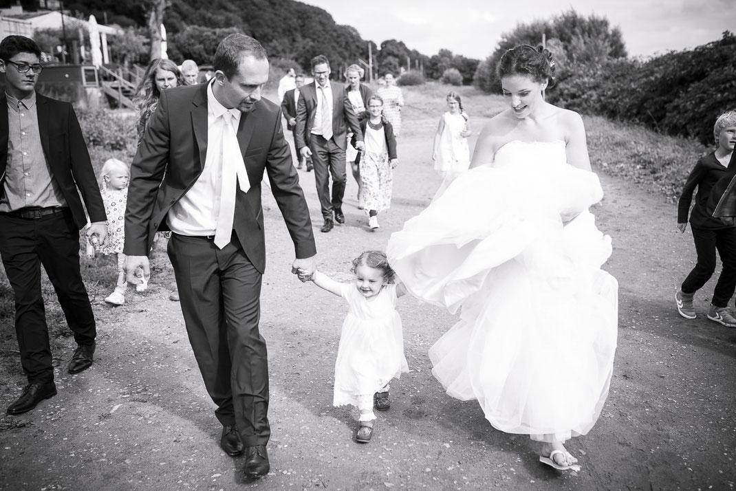 Hochzeitsfotograf Hamburg - Brautpaar auf dem Weg zum Welbstrand zum Brautpaar-Shooting mit wehendem Hochzeitskleid