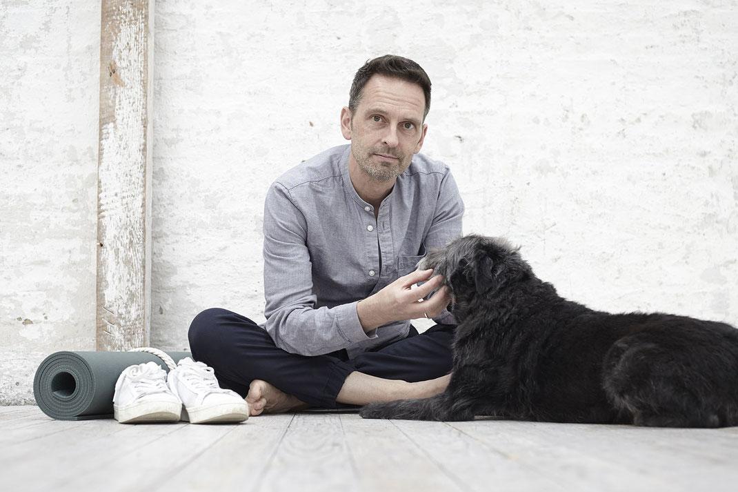 Yogalehrer Andreas mit seinem heraufschauenden Hund Bastian