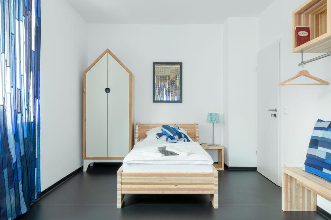 Other Side - Dieses Mobiliar besteht aus individuellen Holzplatten, die sich aus der Addition recycelter Materialstreifen zusammensetzen.