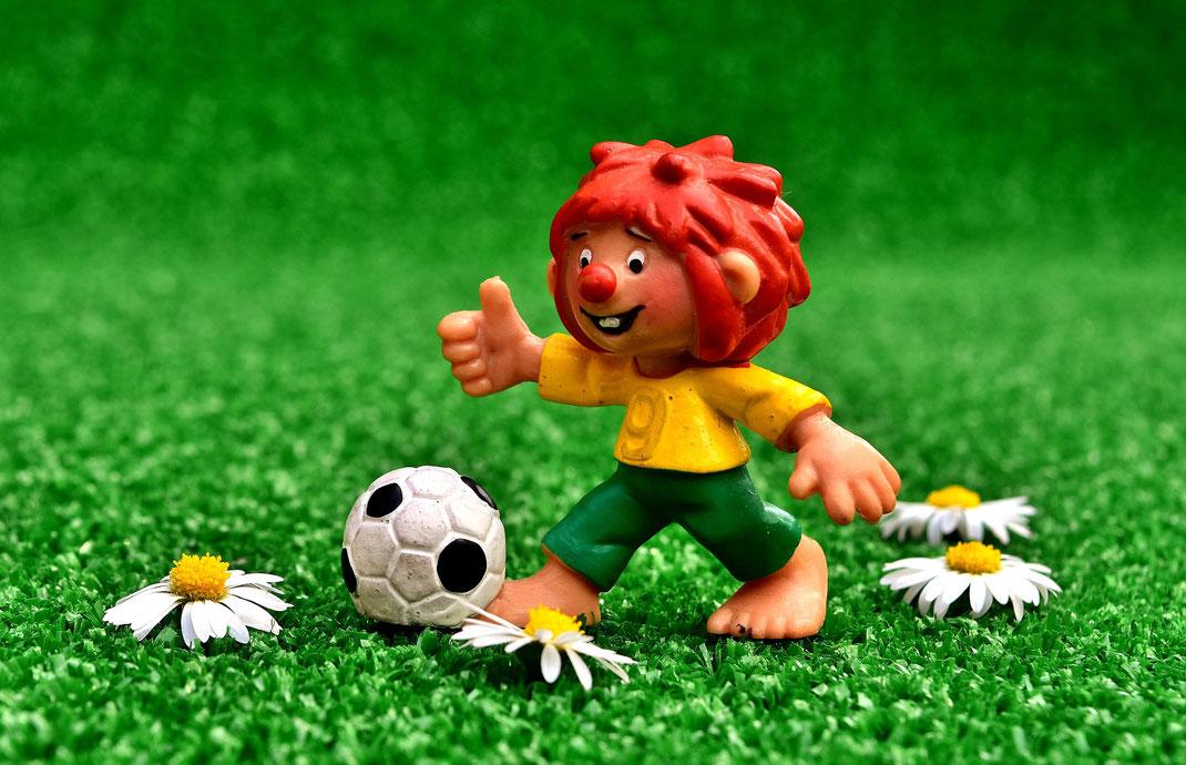 Pumuckl-Figur auf einer Wiese mit Fußball