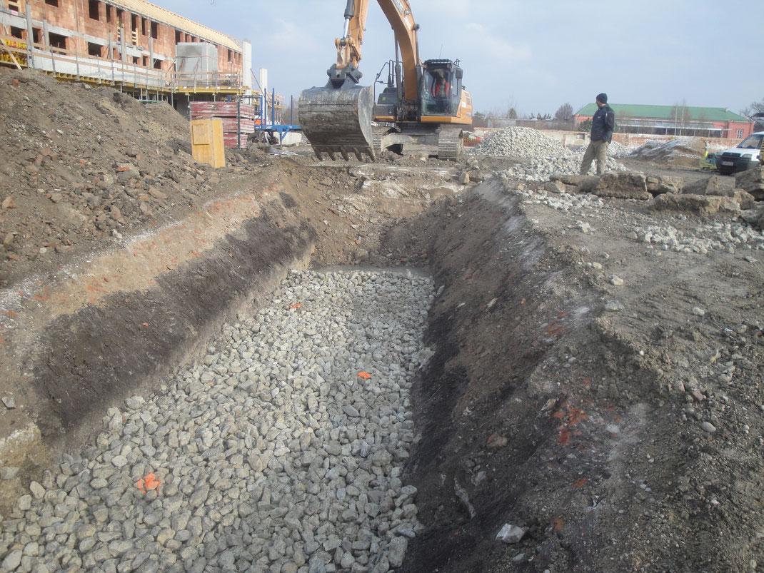 Schaufelbagger vor einer Baugrube und im Hintergrund eine Wohnhausanlage im Rohbau.