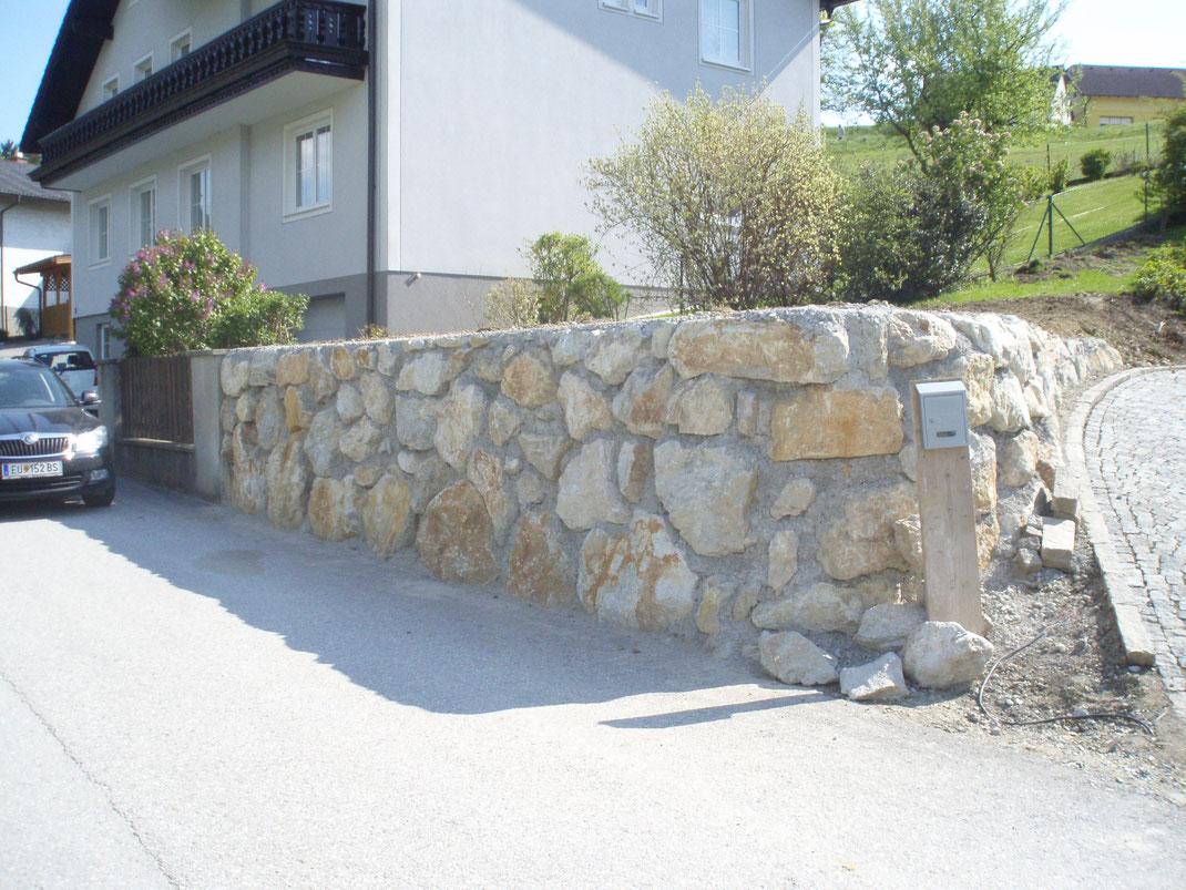Garten von Steinmauer umrandet.