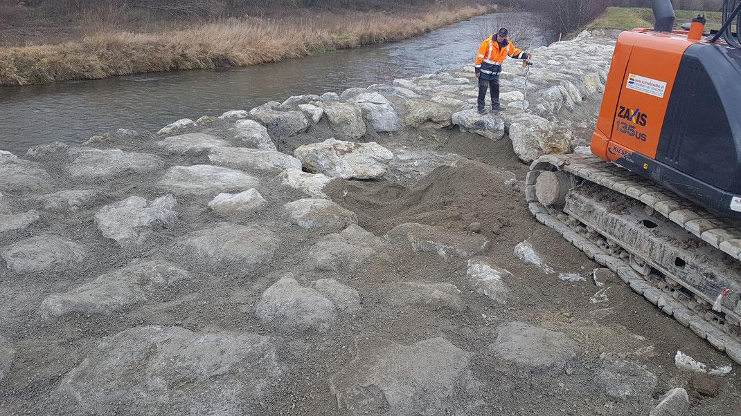 Flussufer mit Steinen befestigt mit einem Arbeiter und einem Bagger darauf.