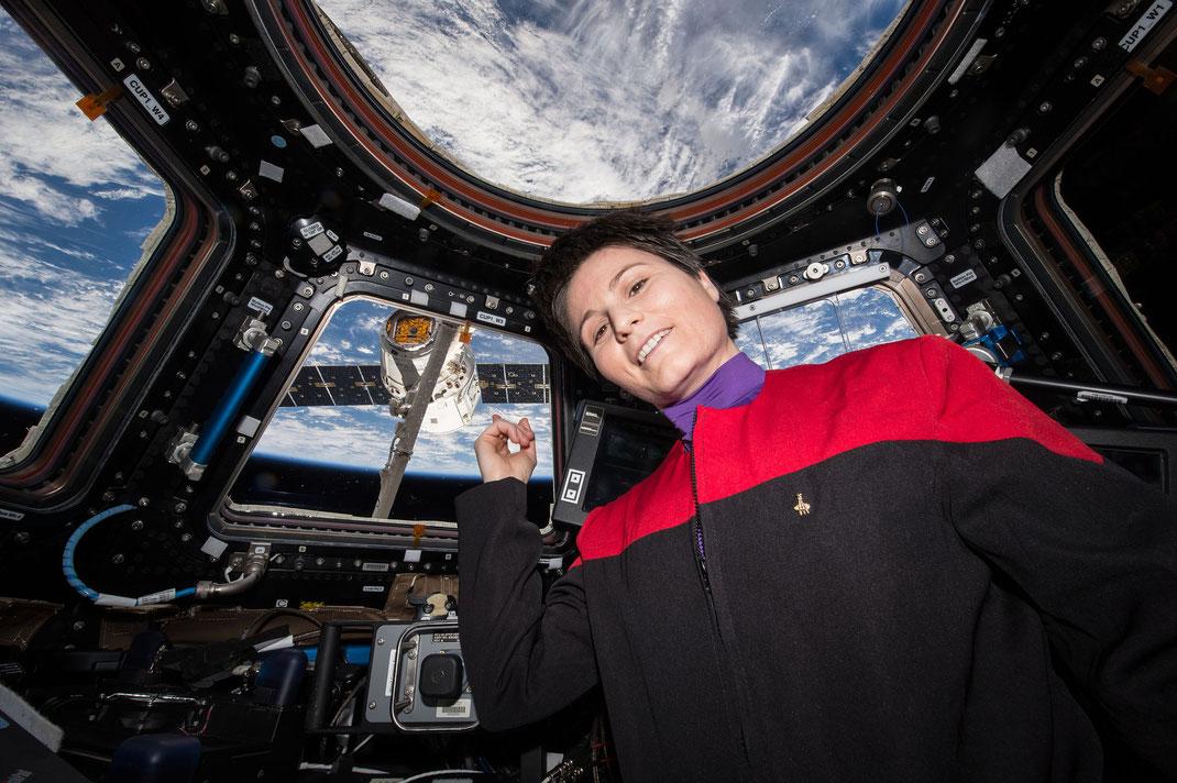 Astronautin blickt aus der Raumstation ISS ins Weltall.
