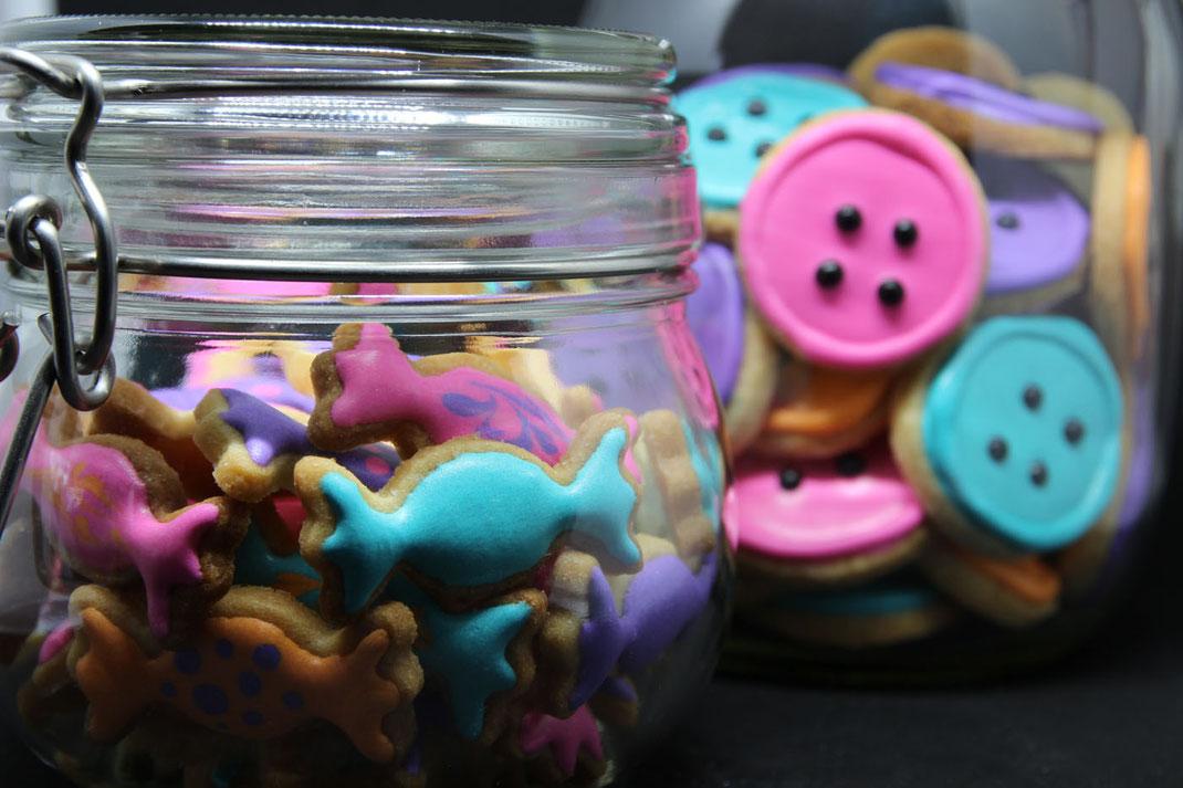 Bonbongläser mit lustigen Keksen in Bonbon- und Knopfform