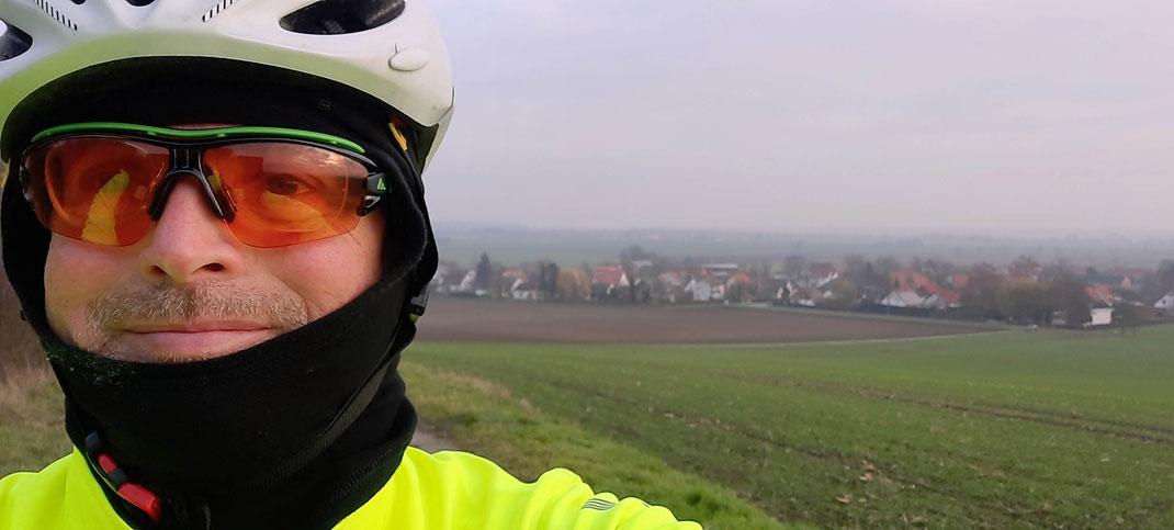 Ein Radfahrer mit Helm und Brille steht vor einem Dorf im Nebel.