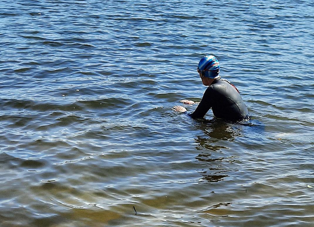 Eine Schwimmerin schwimmt in einem See. Sie trägt einen Neoprenazug und eine Bademütze, um sich vor der Kälte zu schützen.