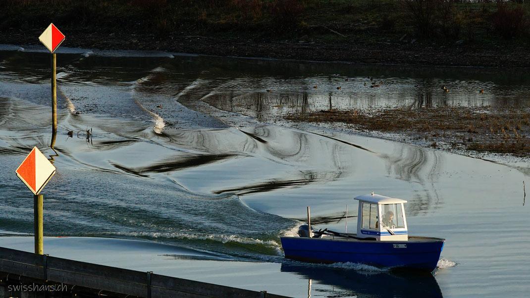 Blaues Fischerboot auf dem Heimweg vom Fischfang auf dem alten Rhein bei Altenrhein erzeugt zauberhafte Wellen.