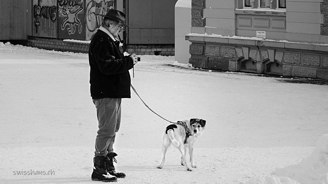 Fotograf mit Hund an der Leine auf einem schneebedeckten Platz.