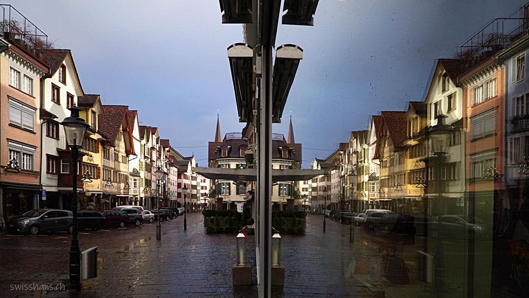 Antike Häuserreihe der Marktgasse von Altstätten spiegelt sich im Schaufenster.