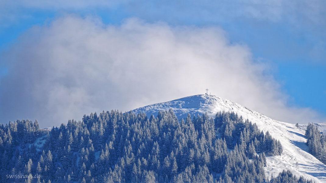 Bergkuppe vom Berg Hohe Kugel. Schneelandschaft mit blauem Himmel und weissen Wolken. Zwei Menschen beim Gipfelkreuz.