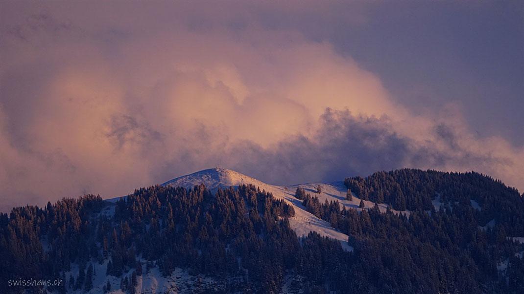 Der Berg Hohe Kugel in rötlicher Abendstimmung mit Schnee und rötlichen Wolken