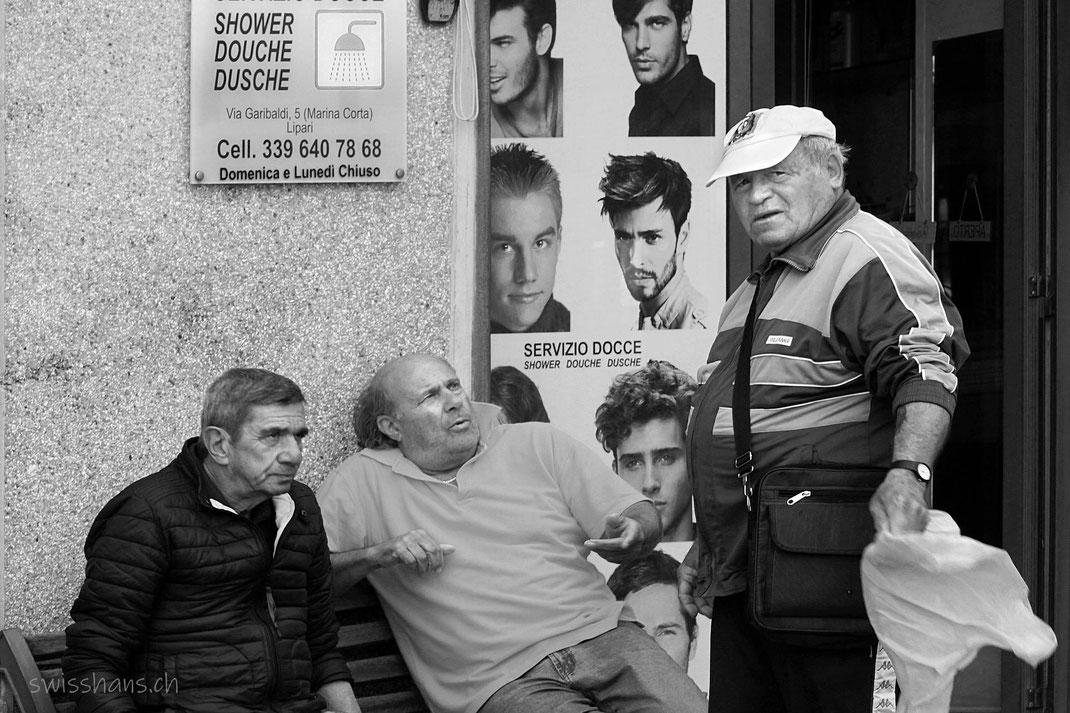 Drei Männer sitzen auf einer Bank vor dem Eingang zu einem Dusche-Salon