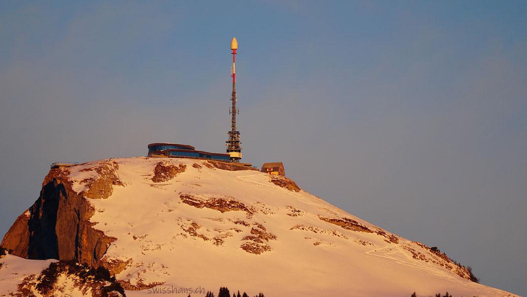 Der verschneite Berg Hohe Kasten mit Drehrestaurant und Sendeturm im warmen Morgenlicht.