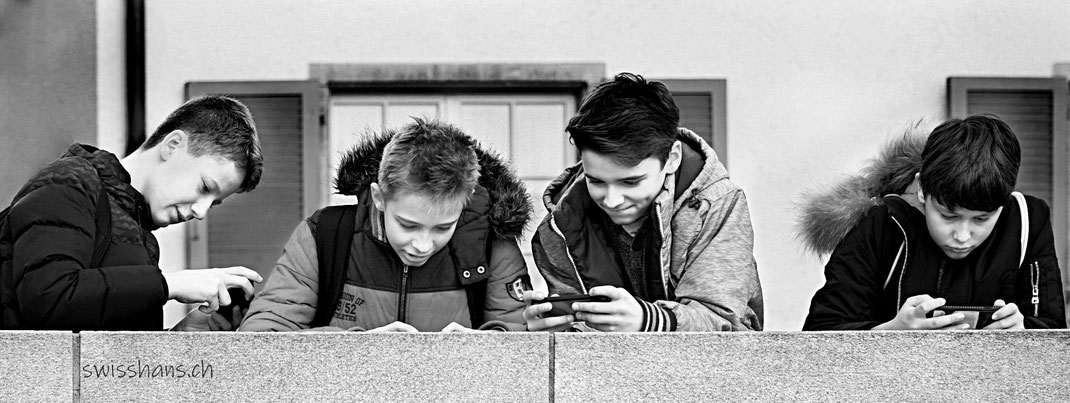 Vier Knaben mit Smartphone auf einer Mauer vor einer Hausfassade.