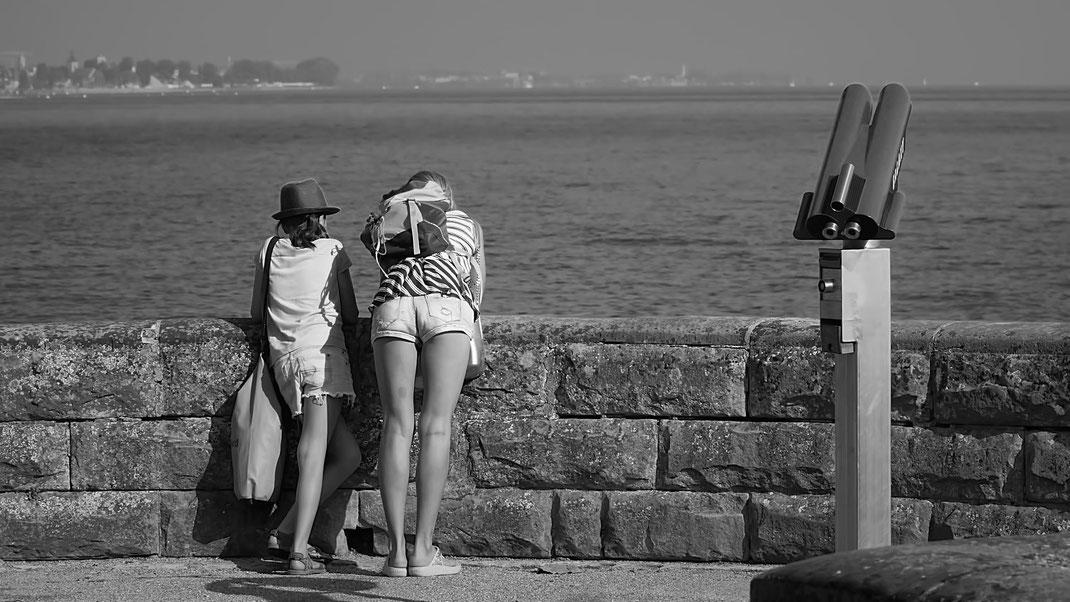 Eine junge Frau und ein Mädchen blicken neben einem Fernrohr auf den Bodensee
